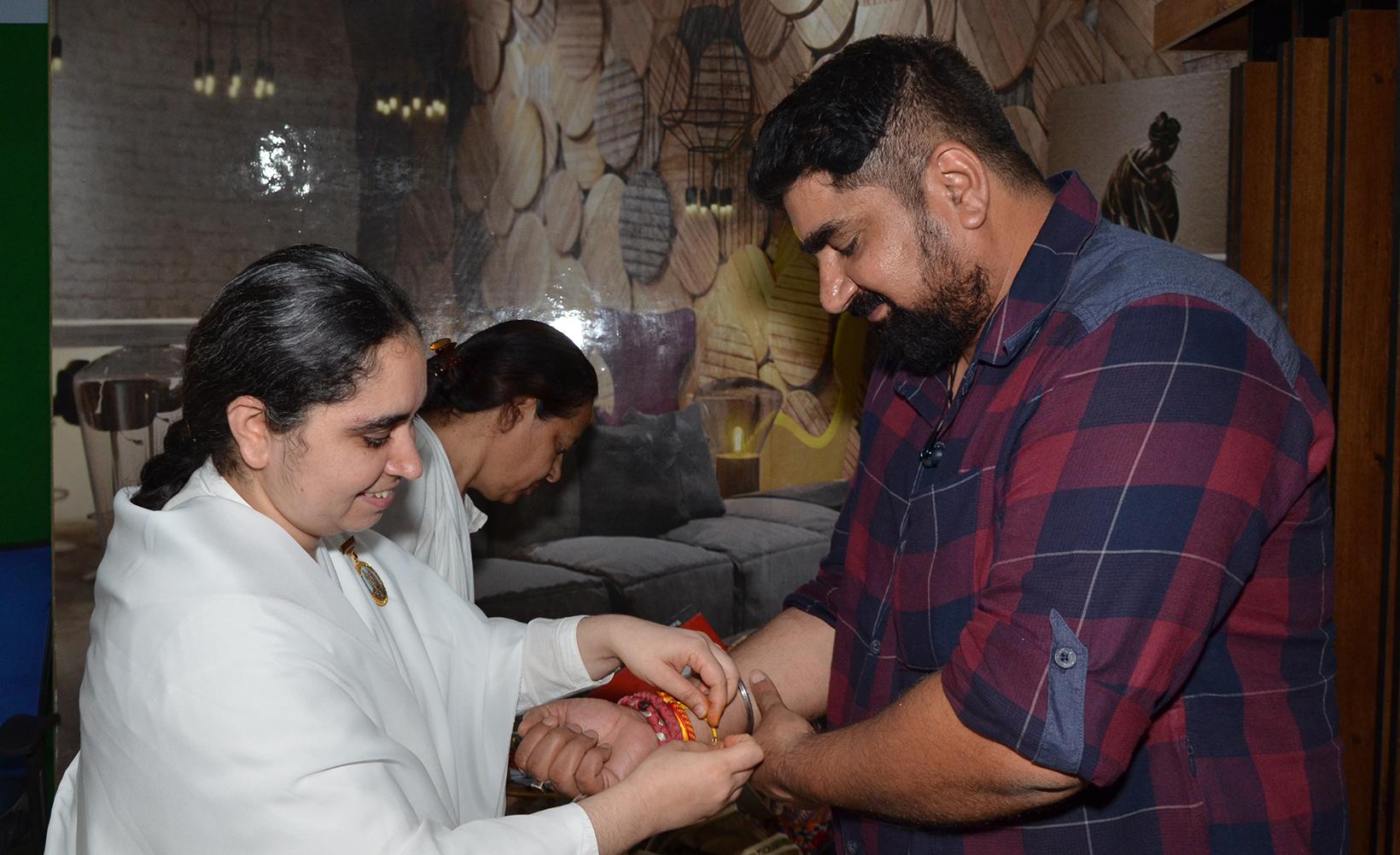 BK Aditi from Gyan Sarovar Mount Abu tying Rakhi to Mr.Satish Tiwari